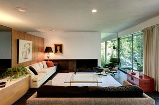 The living room features a brick-inlay fireplace and a wall of glass with serene forest views.