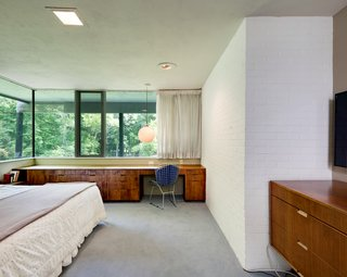 The master bedroom also features expansive glazing and built-in cabinetry.