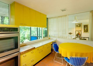 The kitchen features original, bright yellow St. Charles cabinetry.