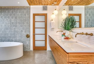 The stylish master bath is a mix of beautifully patterned porcelain tiles and wood.