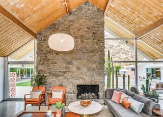 The open living space features a 16-foot-tall tongue-and-groove ceiling, and it's anchored by a bold stone fireplace.