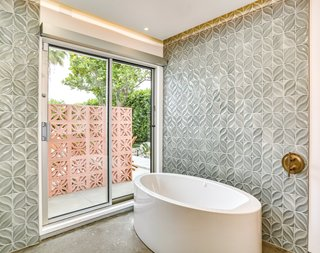 Even the bath has outdoor access. The tiles echo the pattern on the brise soleil.