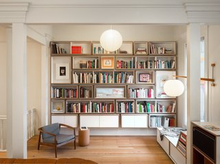 The family loves books. This wall of bookshelves was custom-designed by Bohlin Cywinski Jackson and fabricated by Tomlinson Woodworks. A bespoke reading nook is on the right.