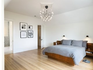 The light-filled master bedroom features hardwood floors and lighting from Mooi.