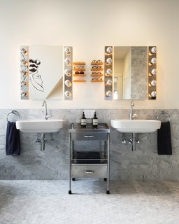 The bathroom features wall-mounted Duravit washbasins and custom shelves for eyeglasses.