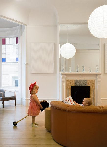 The Freeman children play in the living room, which features an elegantly carved fireplace.