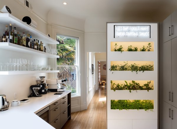 The kitchen enjoys natural light and features white Corian counters, custom powder-coated aluminum shelves, and a WallyGro greens wall with automatic watering and lighting integration. The family uses the greens and herbs in their meals.