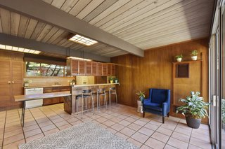 The wood-paneled kitchen, which has a breakfast bar and an extended countertop, overlooks a cozy den.