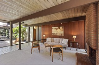 Tongue-and-groove ceilings, mahogany-paneled walls, and a glass wall opening the living space to the atrium are classic Eichler characteristics.