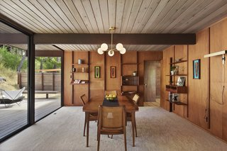 The dining room, which organically extends from the living room, opens to a deck via sliding glass doors.