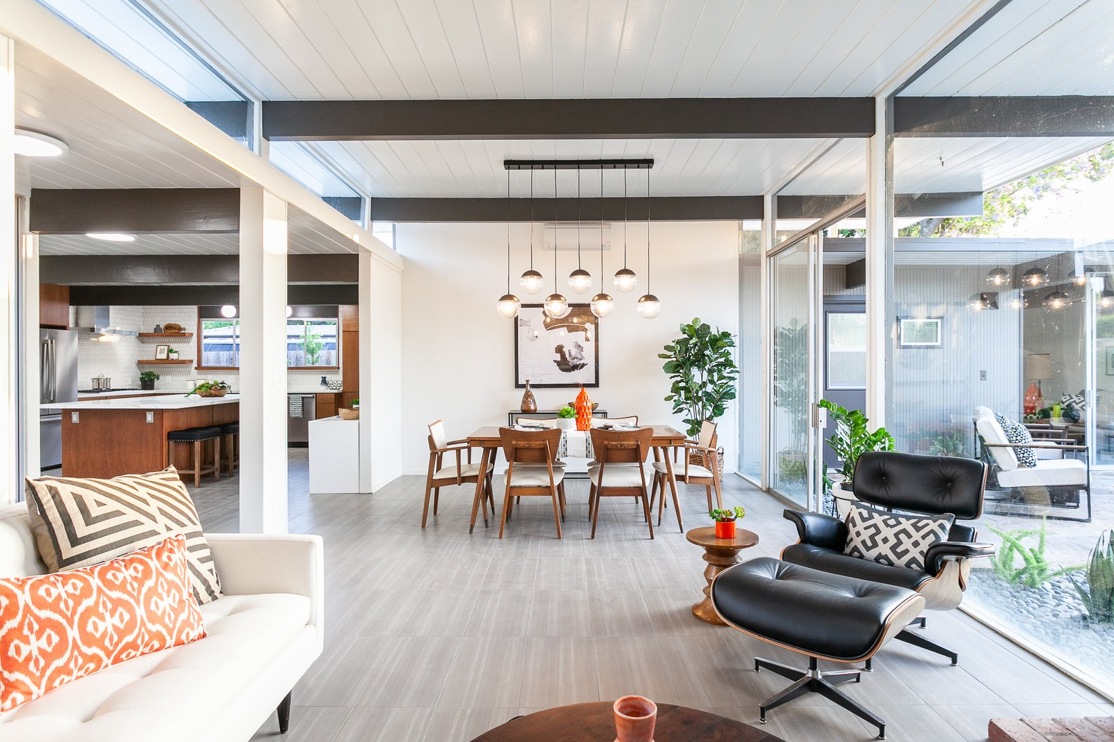 The living and dining room feature a wall of glass and a classic tongue-and-groove ceiling.