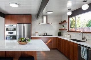The kitchen renovation introduced a center island, stainless steel appliances, and a stylish tile backsplash.