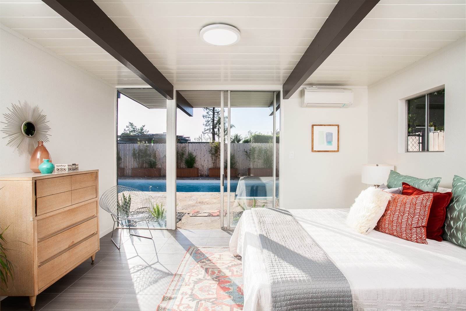 Bedroom, Table, Night Stands, Ceiling, Dresser, and Bed The master bedroom features sliding glass doors which provide direct access to the backyard pool.  Best Bedroom Bed Night Stands Dresser Ceiling Photos from A Spacious and Stylish Orange County Eichler With a Pool Seeks $1.25M