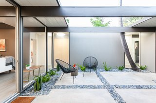 Like other Eichler homes, this 1964 model designed by Claude Oakland and Jones & Emmons opens to a spacious central atrium, which has been updated with concrete pads bordered by loose stones that house local succulents under the semi-enclosed space. Deep eaves allow for some shade, while a larger central portion remains open for trees and sunlight.