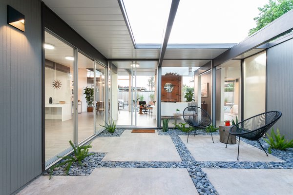 Sliding glass doors connect the atrium to the home's living space.