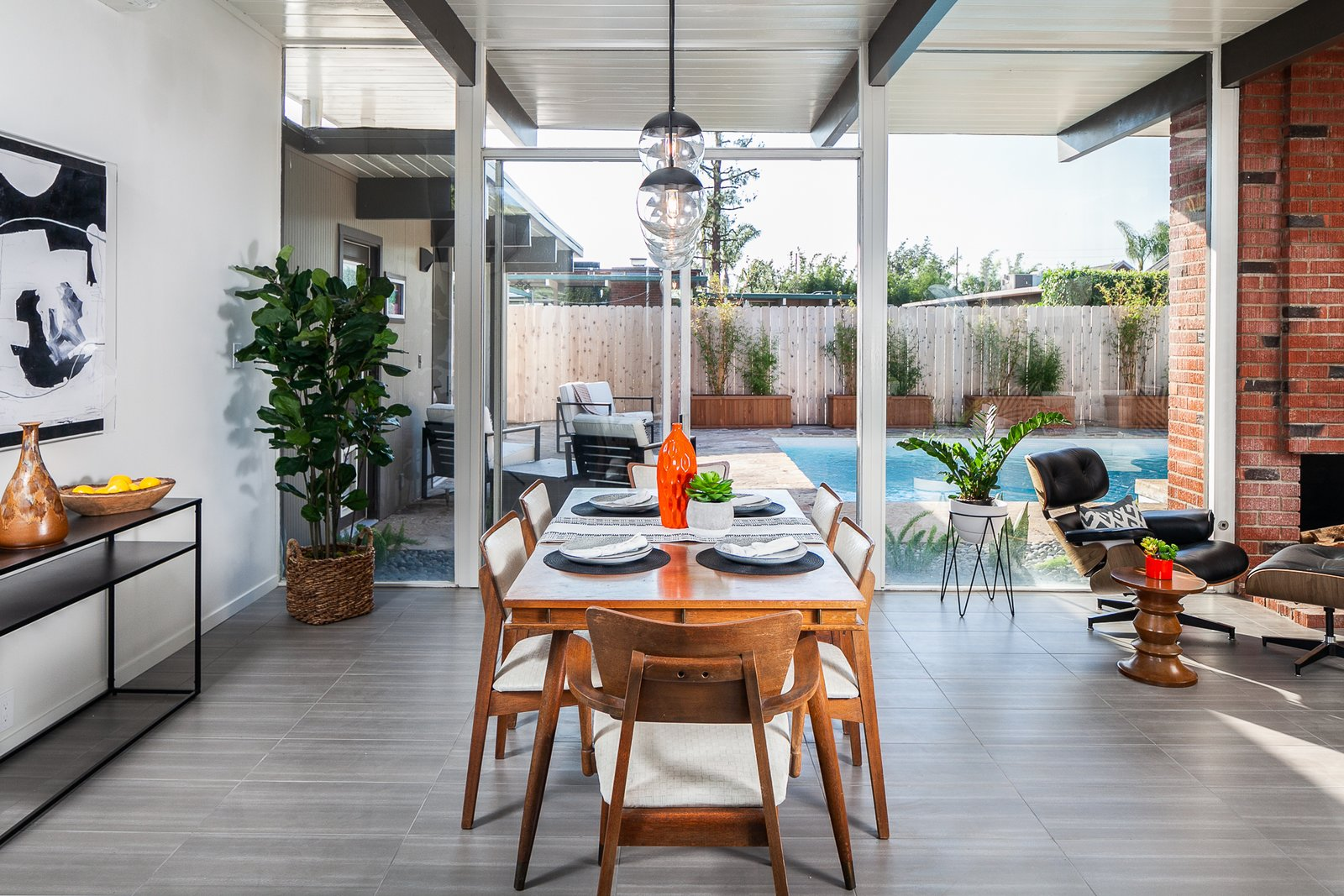 Dining, Standard Layout, Wood Burning, Pendant, Chair, and Table The dining and living also overlook the backyard pool.  Best Dining Wood Burning Table Chair Photos from A Spacious and Stylish Orange County Eichler With a Pool Seeks $1.25M