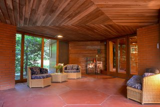 The exterior and indoor/outdoor spaces are a mix of brick and wood paneling. Hexagonal concrete floor tiles create continuity between interior and exterior.