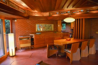 An original built-in dining table and chairs that Wright designed specifically for the house divide the living space from the angular galley kitchen.