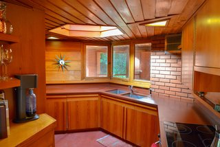 The angular galley kitchen is illuminated by a hexagonal skylight.