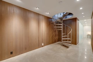 The spiral staircase leads down to the lower level, which houses a large rec room and the master bedroom suite.
