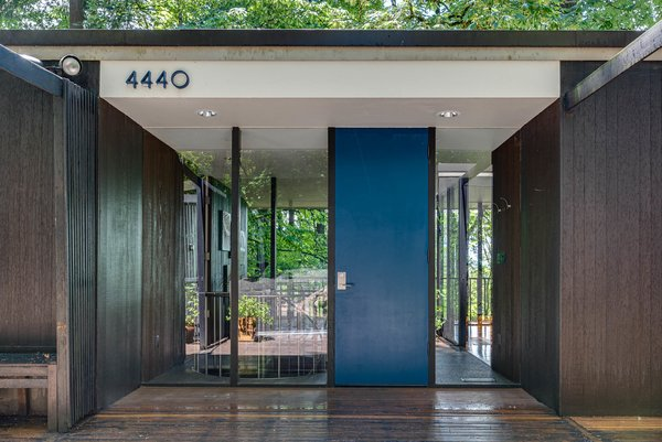 Framed by floor-to-ceiling glass, the bright blue front door adds a pop of color to the facade.