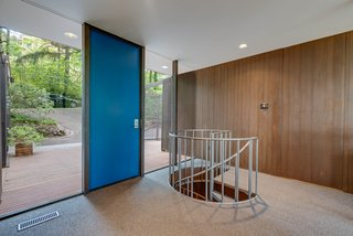 Wood-paneled walls conceal a door leading to the private areas. A spiral staircase descends to the home's lower level.