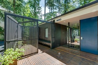 The front facade features two gated deck/lounge areas—one on either side of the door.