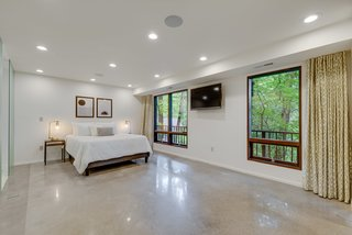 The spacious master bedroom suite enjoys forest views.