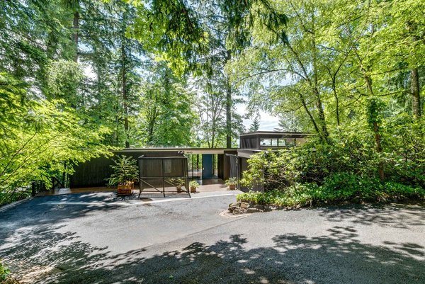 Set in the southwest hills of Portland, Oregon, this 1965 home was designed by noted local architect William Fletcher and entirely renovated in 2008. The low-lying home with a bright blue door was customized with elements that complemented the original midcentury architecture, including updates to all bathrooms, opening up the kitchen and adding cabinetry in Oregon black walnut, and transforming the car port into a dining room.