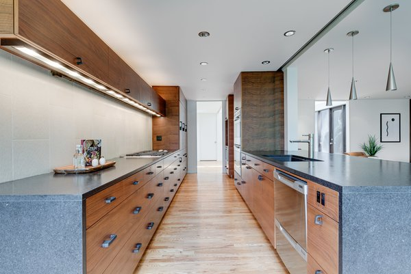 The kitchen cabinetry is crafted from Oregon black walnut, and the countertops are honed Cambrian granite.