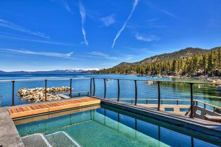 A pool on the deck overlooks the water and the surrounding landscape.