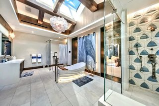 The guest bath boasts skylights overhead and a giant soaking tub set against a backlit slab of marble.