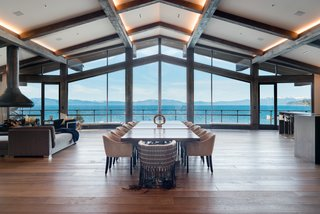 The great room features floor-to-ceiling windows, a floating fireplace, exposed beams, lofty vaulted ceilings, and a multimillion-dollar view.