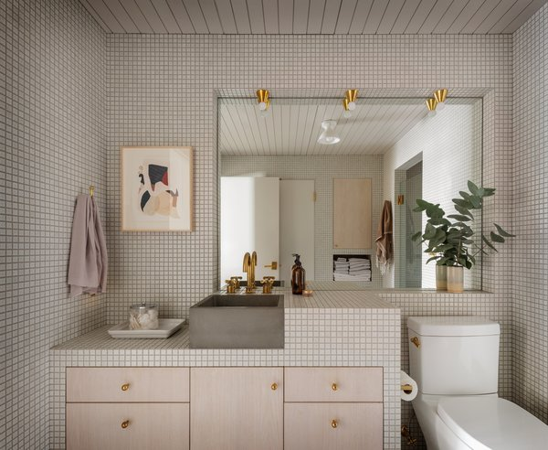 """The contractors working on the project started referring to the bathroom as a """"jewel box"""" because of the meticulous attention required to piece it together. """"The 1"""" x 1"""" Japanese porcelain tiles were laid out in a grid that aligns with every element in the bathroom,"""" says Eng-Goetz. """"For example, the bathroom sink aligns with the adjacent grout lines, as do the inset cabinet doors below."""" The cabinetry is white-washed red oak and the vanity lights are by Anastassiades."""