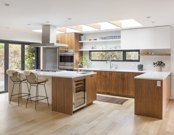 As a pastry chef who is also left-handed, Nicholas knew exactly how she wanted her kitchen renovation to play out so that it would best suit her own personal needs. The walnut cabinetry was custom made by L&Z Specialties and topped with Caesarstone countertops. The kitchen island features Bertoia barstools, a SubZero wine cooler, and a Wolf gas cooktop. The flooring is white oak. Andrea also has a Wolf double wall oven that meets her baking requirements.