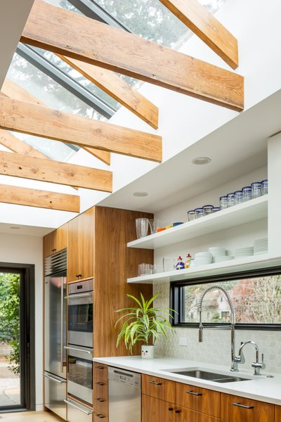 "To make sure that the kitchen would be flooded with natural light, a skylight was inserted. ""Ellen Wu, the project lead, came up with a fun detail: We exposed the roof framing to keep a wood element in the ceiling,"" explains Boyer. The backsplash tiles are the Dwell Pattern Little Diamond Mix from Heath Ceramics."