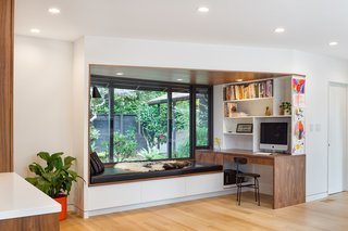 Boyer inserted a home office just off the kitchen so that Nicholas could have designated office space and also a home for her cookbooks. The built-in bench (which also houses storage drawers underneath) is a popped boxed window which is visible to the left as you enter the home.