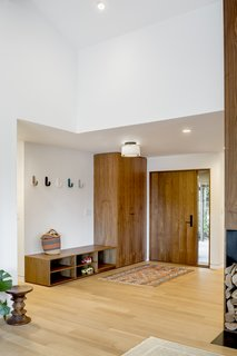 The entry features a walnut door and storage cabinets from Rejuvenation. The light fixture is from Cedar & Moss.