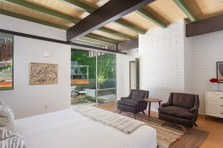 The master bedroom also opens to the outdoor space via sliding glass doors.