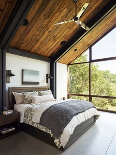 The master bedroom has a Restoration Hardware bed, wall sconces from Designer Metal Works, and a wall of windows.
