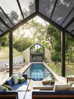 A lap pool fills the expanse between the music studio and the house.