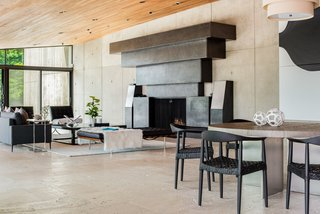 The living space is anchored by an oversized, sculptural fireplace made from blackened steel by David Edelman. The design incorporates graduated rectangular tiers and is flanked by matching sound speakers.