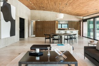 The great room comprises an open-plan living, kitchen, and dining area. The Travertine tile flooring features radiant heat. Oversized sliding glass doors lead out to an outdoor terrace, while the ceiling is paneled in teak.