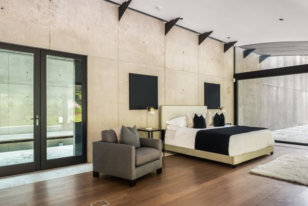 The master bedroom is privately located off the main house in a  rectangular tower towards the back of the home. The master is complete with custom touches like distressed blackened steel steps that lead down to a private basement garage, as well as cantilevered steps up to a penthouse office.