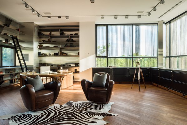 The penthouse office has an open workspace with a diagonally-laid teak floor, built-in metal mesh shelving, and a built-in blackened-steel credenza that wraps the edge of the room. There are also cantilevered floating steps which lead to the rooftop observation deck.