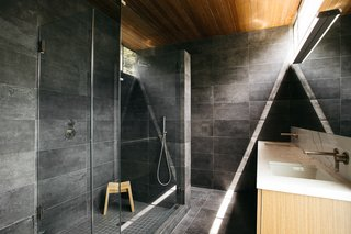 The master bathroom renovation was designed by Asaf Mordoch and completed in August 2019. The intention of the remodel was to modernize the bathroom and to incorporate nature, light, and midcentury elements into the space. The redesign also picks up on elements of gray to visually tie the space to the living room. The material palette includes black Italian porcelain and Carrara marble countertops.