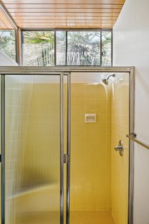 The second bathroom has clerestory windows and features cheery, yellow tiles. It is from the original 1958 construction.
