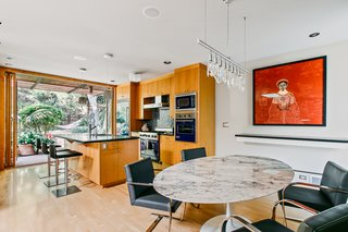 The open kitchen and dining area is bright, airy, and features a custom-made retractable glass door to mirror the other side of the open-plan space.