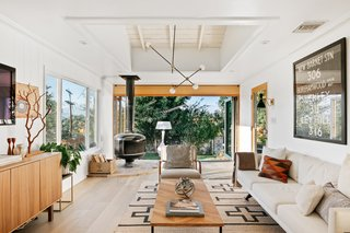 The open floor plan features a whitewashed interior, beamed wood ceilings, splashes of hardwood, and a freestanding vintage fire drum fireplace sourced by Wilson's wife Coco.