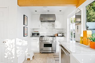 The marble backsplash extends up to the range hood, emphasizing the sense of height in the kitchen.